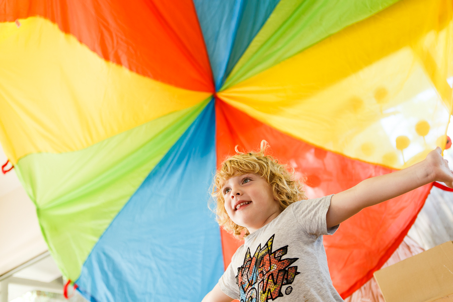 Child playing under colourful fabric in classroom at Papilio Ashburton